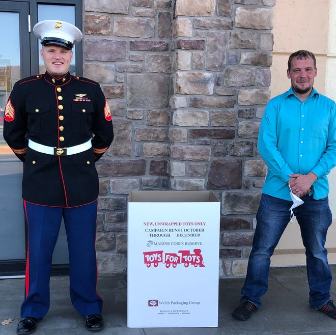 Sgt. Joshua Mikalunas, a Hornell-based U.S. Marine Corps recruiter, and Steve Olix of Turning Point stand with a Toys for Tots collection box Monday at the Marine Corps Recruiting office in Hornell. Mikalunas and Olix announced the Kick off of the 2020 Marine Corps Reserve Toys for Tots campaign in the Canisteo Valley.