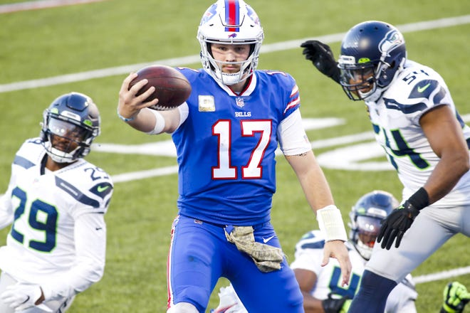 Buffalo Bills quarterback Josh Allen (17) rushes past Seattle Seahawks Bruce Irvin and Jayson Stanley for a touchdown during the second half of Sunday's game in Orchard Park, New York.