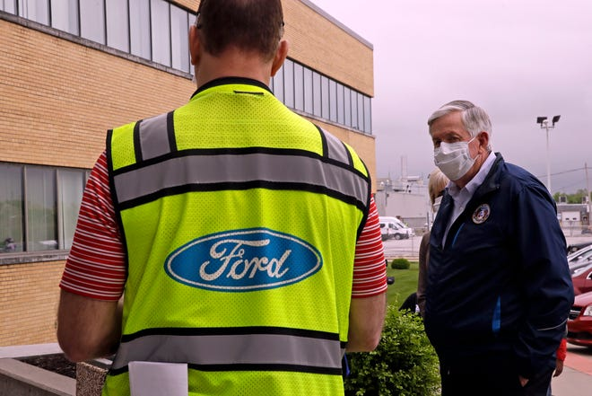 Missouri Gov. Mike Parson talks to a Ford representative outside Ford's Kansas City Assembly Plant in Claycomo, Mo., in this file photo. Ford plans to add 350 jobs at two U.S. factories to meet expected demand for electric vehicles that haven't gone on sale yet. The automaker says it will add 150 workers at Claycomo to build the new E-Transit full-size van that is scheduled go on sale late next year.
