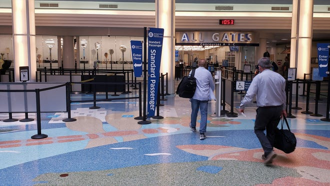 Only a handful of masked passengers head to the TSA checkpoint late Tuesday morning at Jacksonville International Airport.
