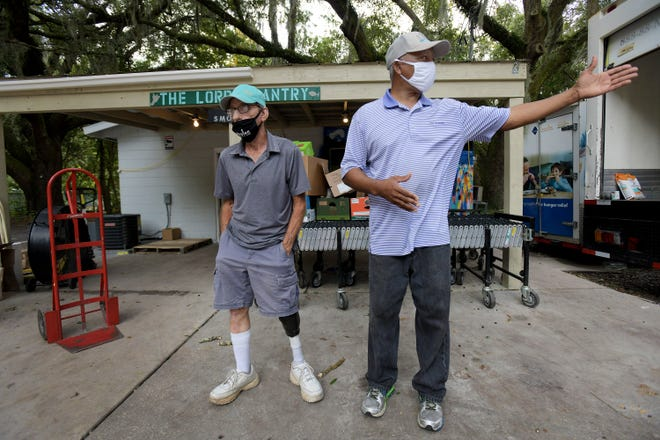 Vietnam veterans Rick DuMiller (left) and Charles Green stand in front of the food pantry they manage on Jacksonville's Westside. Both first visited The Lord's Pantry as customers, Green bringing a friend to get food, DuMiller to get food himself.