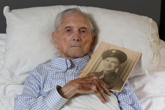 Lt. Col. Joseph Wood, who fought in World War II, Korea, and Vietnam, holds a picture of himself taken in 1945 when he was 20 years old, at his home in Delaplane, Virginia.