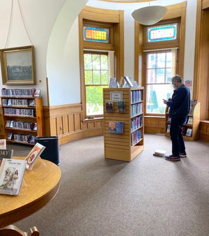 Holden resident Richard Johnson browses Gale Free Library's new mini-collection.