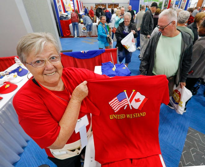 """Rin VanHemert, a resident of Canada, holds up a """"United We Stand"""" T-shirt during the Snowbird Extravaganza at the RP Funding Center in Lakeland in January."""