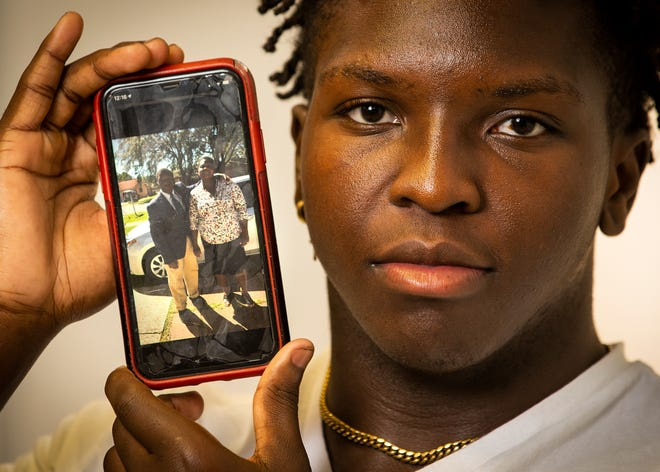Eleazer Quetant, a senior defensive end at Dunnellon High School, holds a picture of himself when he wore suits to school as a freshman while standing next to his mother, Erna. Quetant talked about losing his parents after they were murdered in Haiti in September, and his life since.