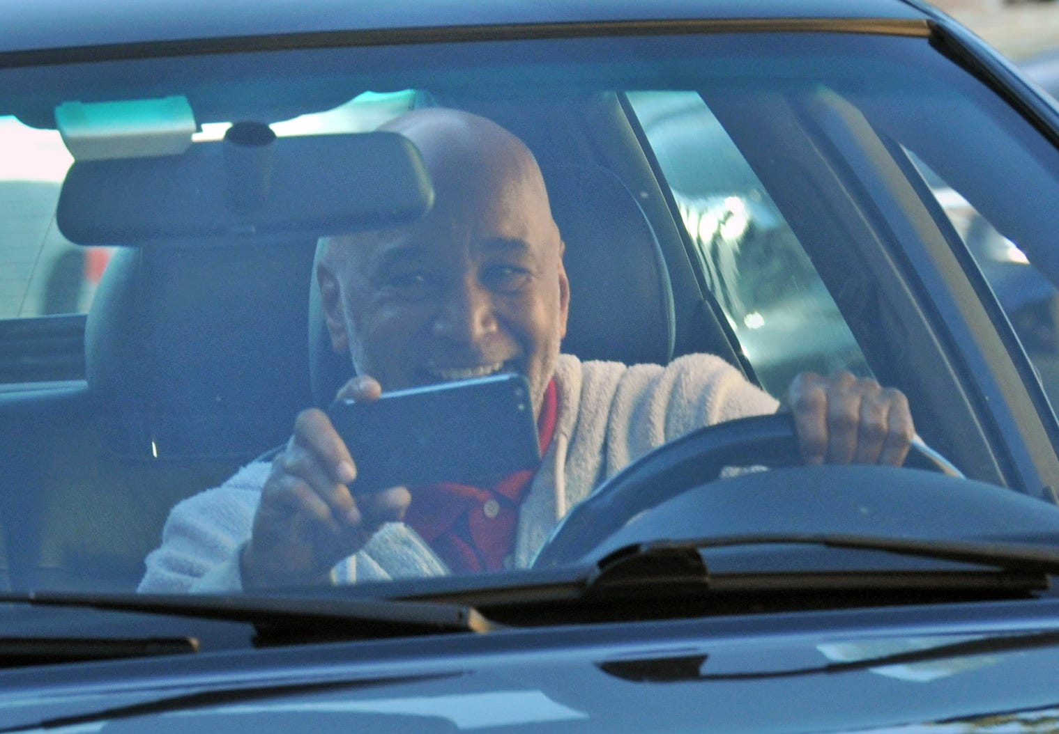 A grandparent is all smiles as he drives pasts students waving flags and signs during the St. Mary of the Hills School's Grandparents/Veterans Day drive-through in Milton, Tuesday, Nov. 10, 2020.