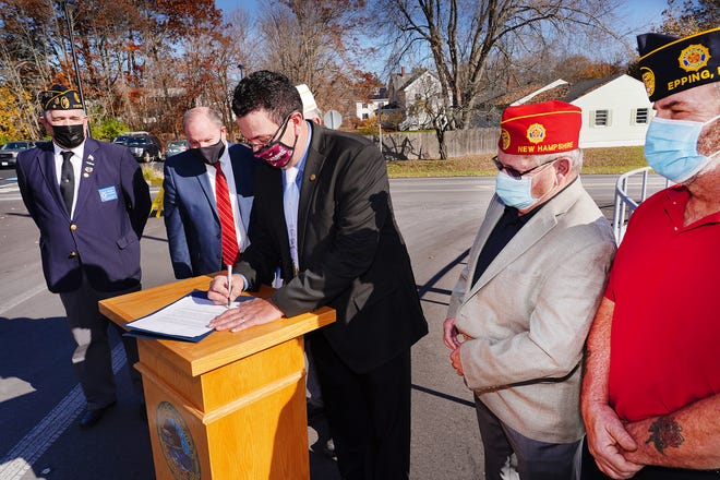 Portsmouth Mayor Rick Becksted, center, signs the national pledge to help end veteran homelesssness Tuesday surrounded by Frank Desper, post commander of Booma Post 6 of the American Legion, left, David Tille, U.S. Department of Housing and Urban Development New England regional administrator, Ken Maynard, and Bill LeBright, members of the Epping American Legion Post 51.