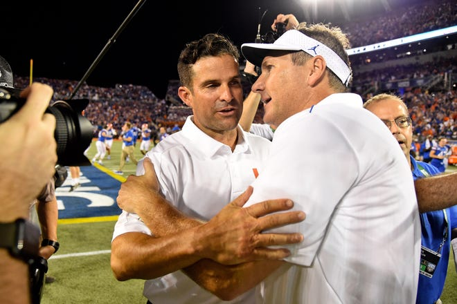 Miami coach Manny Diaz and Florida coach Dan Mullen meet at midfield following the Gators' victory to open the 2019 season. The two teams could close the 2020 season in the Orange Bowl. [Jasen Vinlove-USA TODAY] Sports