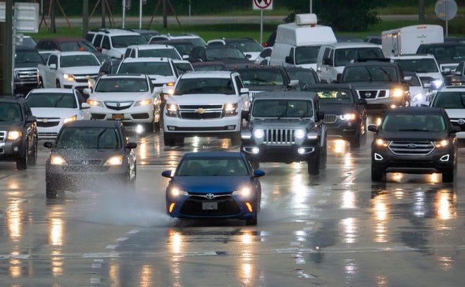 Cars head west on Okeechobee Boulevard in the rain during the morning commute in West Palm Beach Tuesday, Nov. 10, 2020.