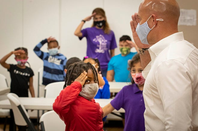 Robert Gooding, 8, (center) learns how to salute Tuesday from U.S. Rep Brian Mast during a Veterans Day education program at the Edna W. Runner Tutorial Center in Jupiter.