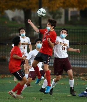 Members of the Tiverton boys soccer team, in white, look for the ball during a game against PCD on Nov. 10.