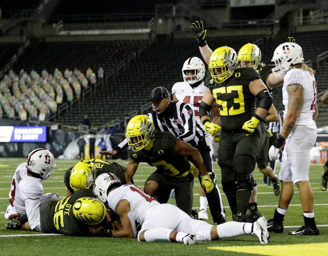 Oregon offensive lineman Ryan Walk (53) celebrates running back Travis Dye's touchdown run in last season's 35-14 season-opening win over Stanford at Autzen Stadium.