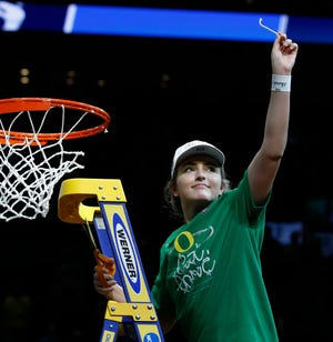 Taylor Chavez holds up a slice of net after the Ducks' 88-84 win over Mississippi State in the 2019 NCAA Tournament regional final at the Moda Center in Portland. The Ducks advanced to the Final Four for the first time in school history with the win on March 31, 2019.