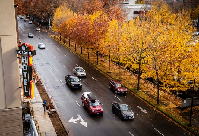 Fall foliage creates a warmly colored corridor on 6th Avenue in Eugene as cars file past the incoming Gordon Hotel. The 5th Street expansion is expected to be completed in the new year.
