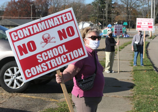 Inez Waddell (left), Melanie J. Roll (center) and Chuck Osborne picket at the site of a new North Canton City Schools K-2 building in North Canton on Tuesday. They contend it is contaminated by chemicals from the former Hoover Co. and too small for a school.