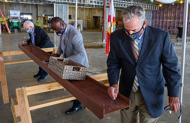 """St. Johns County School board member Bill Mignon, board member elect Anthony Colman and school board member Patrick Canan signed a beam that will used in the district's newest high school under construction on International Golf Parkway before a """"topping out"""" ceremony held on Tuesday."""