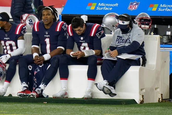New England Patriots quarterbacks Cam Newton (left) and Jarrett Stidham sit on the bench with offensive coordinator Josh McDaniels (right) in the second half against the San Francisco 49ers on Oct. 25, in Foxborough.