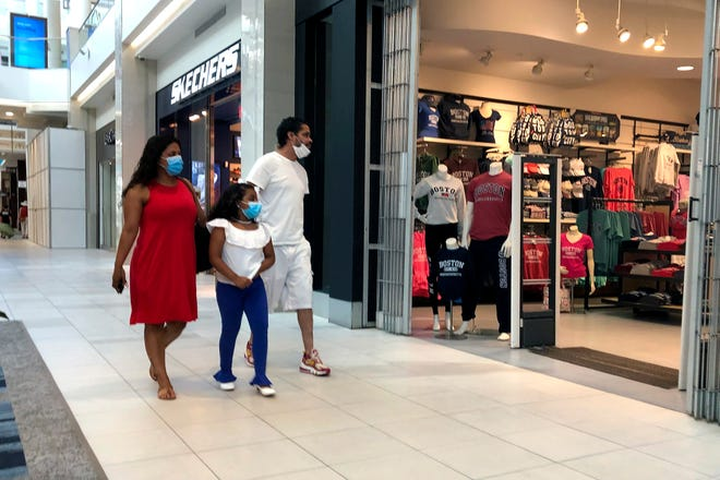 People walk past an open clothing store in June at CambridgeSide mall, in Cambridge, Massachusetts. Holiday shopping across the U.S. will certainly look different this year because of COVID-19.