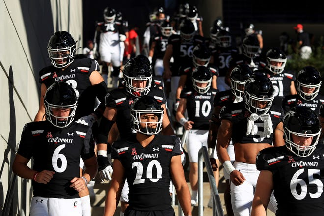 Cincinnati players walk the stairs to the field prior to  Saturday's game against Houston. Cincinnati won 38-10. (AP Photo/Aaron Doster)