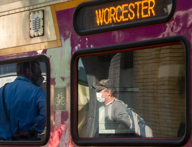 WORCESTER - George Penniman of Leominster is reflected in the window of a rail car as he gets on the MBTA commuter rail train at Union Station Tuesday, November 10, 2020.