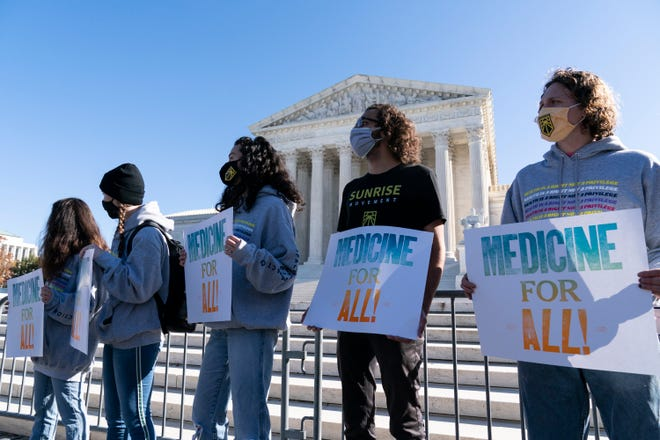 Demonstrators hold signs in front of the U.S. Supreme Court as arguments are heard about the Affordable Care Act on Tuesday in Washington.