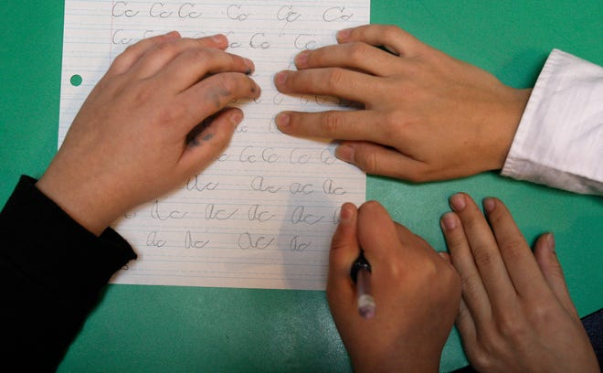 A 12-year-old child with autism works on writing letters during Applied Behavior Analysis therapy with his instructor at the child's home in 2008.