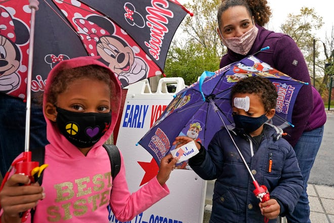 A mother poses with her children after voting early Oct. 29 in Cambridge, Mass.