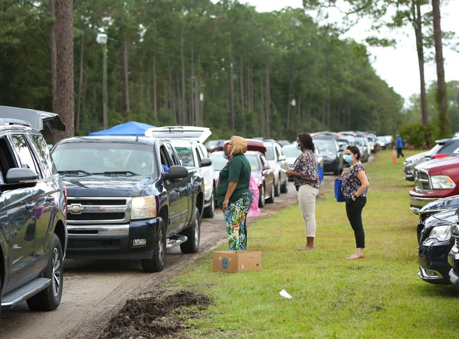 Volunteers talk people waiting in a long line during the annual Strike Out Hunger Food & Turkey Giveaway sponsored by The Long Foundation and Farmshare held at the Alachua County Fairgrounds, in Gainesville Fla., Nov. 10, 2020. [Brad McClenny/The Gainesville Sun]