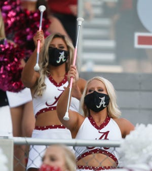 Alabama majorettes wear masks as they perform in the stands at Bryant-Denny Stadium.