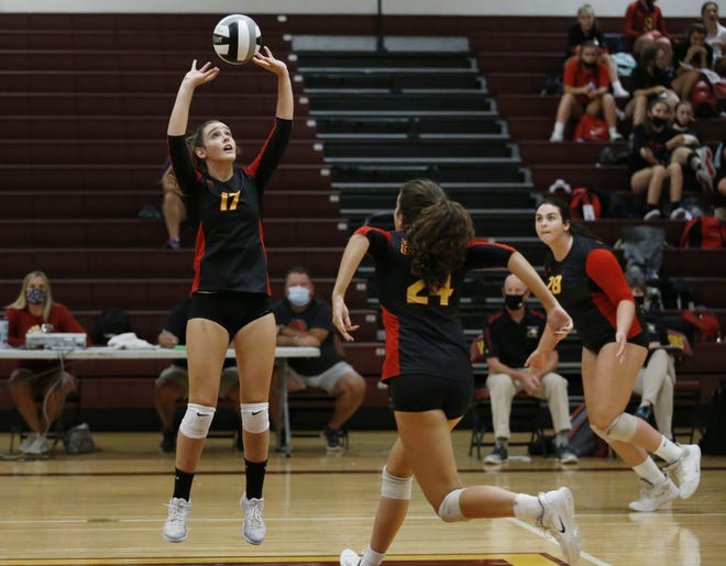 Senior Raegen Bickley sets the ball for junior teammate Andie Stewart, front, as senior Olivia Pollock watches during a match at Westerville North earlier this season. The Golden Eagles, who finished 11-14, overcame injuries to reach a Division I district semifinal.