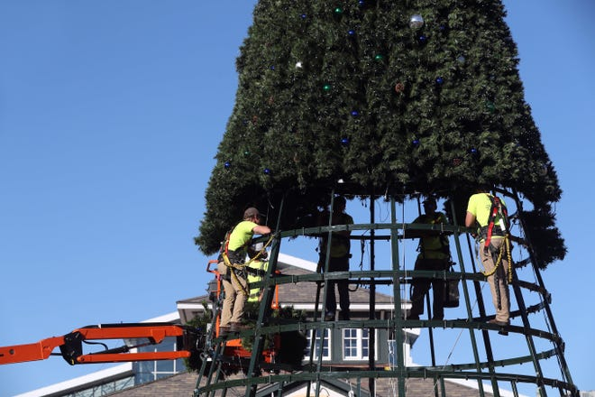 Workers with Zanesville-based Nelson's Seasonal Decor assemble the holiday tree at Easton Town Center, 160 Easton Town Center in northeastColumbus, on Nov. 9. Shopping centers' managers are trying to balance the tradition of attracting holiday shoppers with safety protocols amid the COVID-19 coronavirus pandemic.