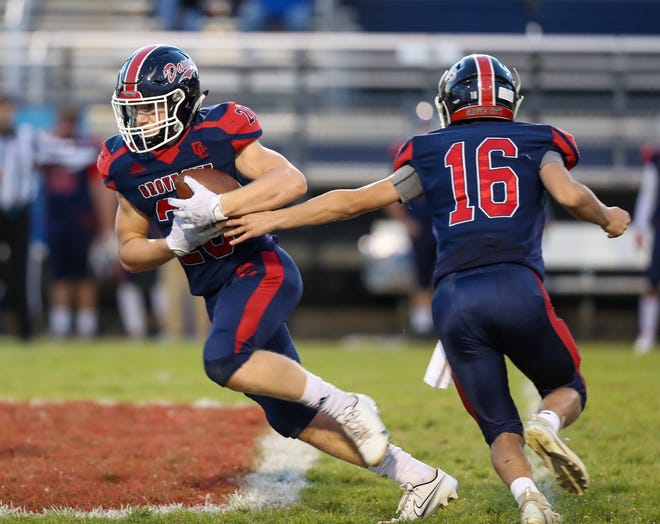 Sophomore running back Trevor Mills takes a handoff from sophomore quarterback Zakk Tschirhart during a 48-12 win over Westland on Oct. 2. Mills led the Dawgs in rushing with 709 yards and seven touchdowns on 127 carries.