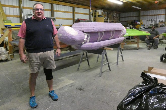 Randy Fischer stands in  Persuader Performance Boats' building next to the 10-foot-long pink foam bratwurst sandwich he and his cousin made in preparation for the Bucyrus Bicentennial kickoff ceremony on New Year's Eve. Business owner Barry Moneysmith is seated at the rear.