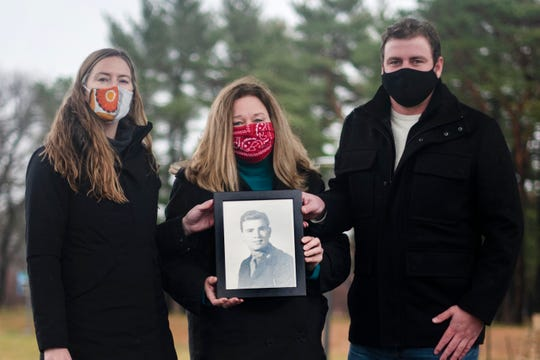 From left, Adrianne, Becky and Zach Greenwald hold a photo of Becky's father, Ed Davis, a Marine veteran who fought in the Pacific theater in World War II and was awarded a Purple Heart. Davis died on Oct. 12 at age 94 from COVID-19.