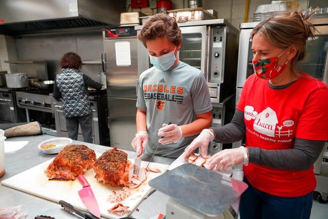 Direktur HealthBarn Foundation Stacey Antine dan relawan Ethan Levy mengukir kalkun yang akan dibekukan dan dikemas menjadi makanan individu untuk lansia di Hawthorne, NJ, pada 3 November 2020.