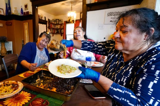 Olga Garcia, right, prepares a plate of food for her sisters Francis Garcia, left, and Anna Garcia at an afternoon family meal Wednesday, Nov. 4, 2020, in the family home in Sedro-Woolley, Wash. On any other Thanksgiving, dozens of Olga's family members would squeeze into her home for the holiday. But this year, she'll deliver food to family spread along 30 miles of the North Cascades Highway in Washington state.