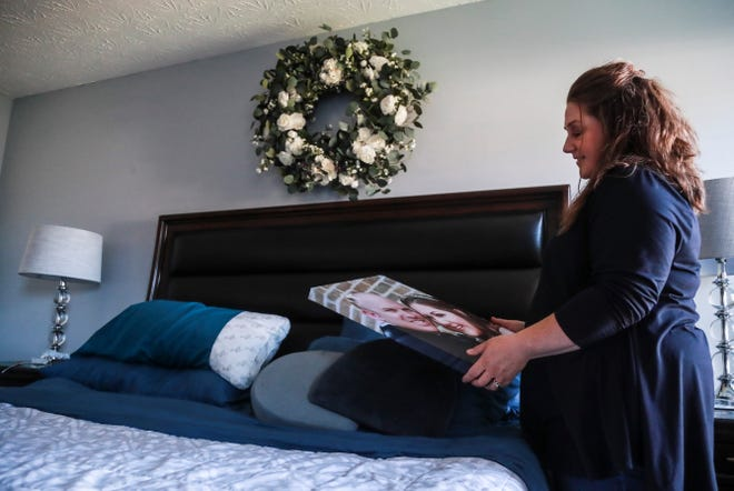 Nicole Keene in her bedroom with pictures of her and husband, Michael, from their wedding day that she plans to hang next to a wreath made from her bridal bouquet. She lost her husband, a 39-year-old veteran, to COVID-19 on Oct. 28.