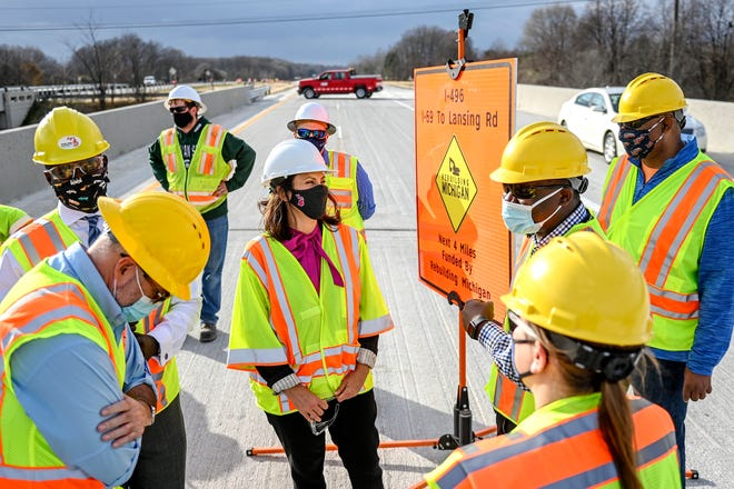 Gov. Gretchen Whitmer, center, talks with MDOT representatives after a press conference announcing the early opening of the rebuild of Interstate-496 on Tuesday, Nov. 10, 2020, near the Waverly Road entrance in Lansing.