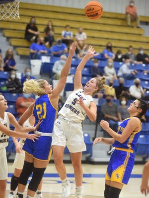 Mountain Home's Cate Jackson (5) lofts a layup over Mountain View's Aubrey Isbell on Monday night at The Hangar.