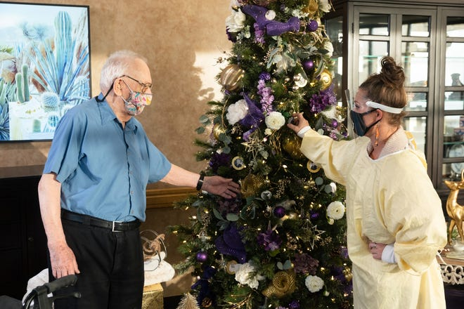 Erienne Luck, right, shows veteran Joseph McKillop the purple heart-themed Christmas tree that she designed for this year's Jubilee of Trees and put up at the Southern Utah Veteran's Home.
