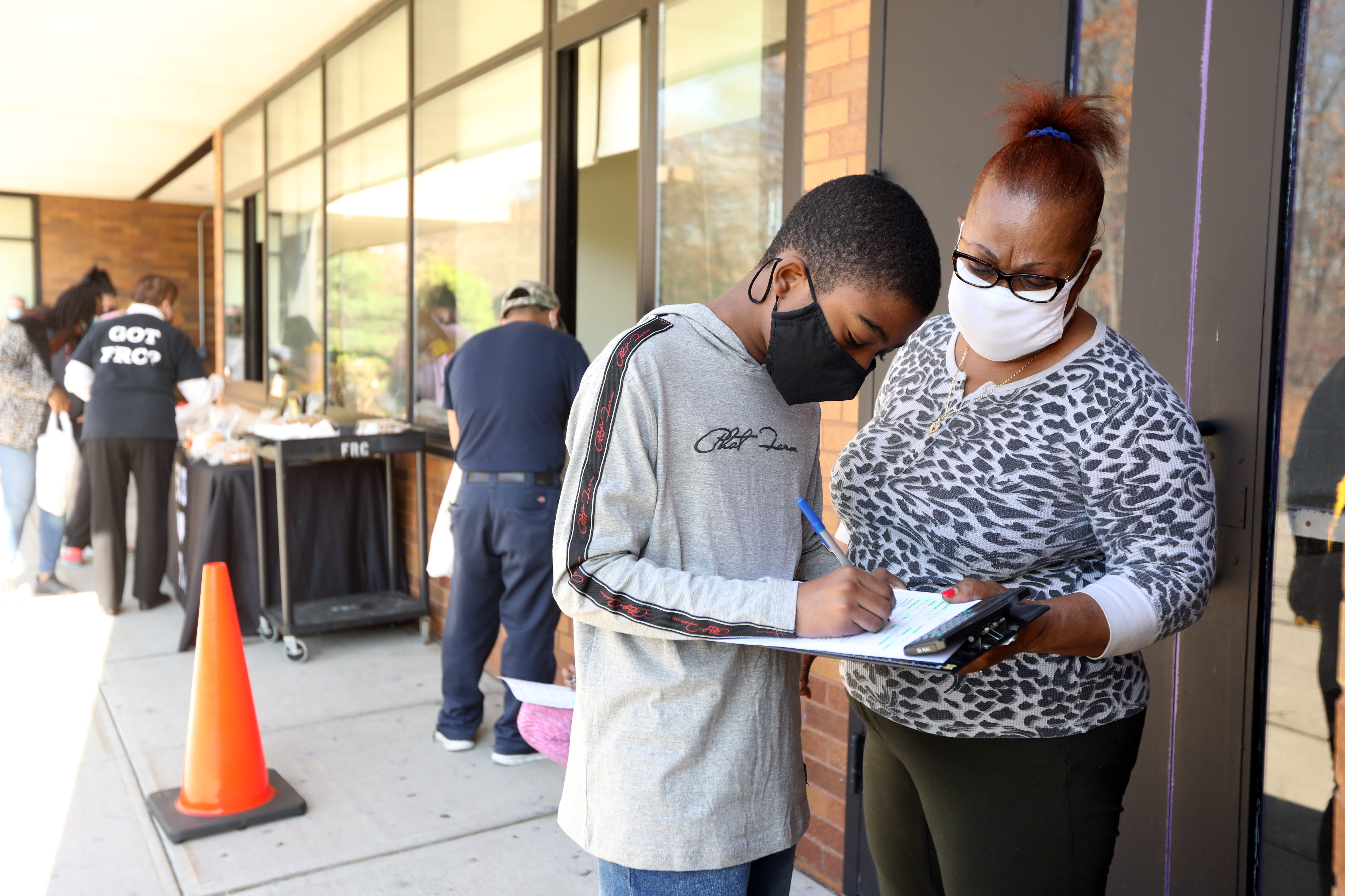 Seventh-grader Lensky Jean-Pierre, 12, and his mother, Gisele, fill out paperwork to receive a Chromebook on Nov. 10 at Chestnut Ridge Middle School in New York. Jean-Pierre had been using his mother's phone for his school work and hoped the Chromebook would make it easier to do his work.