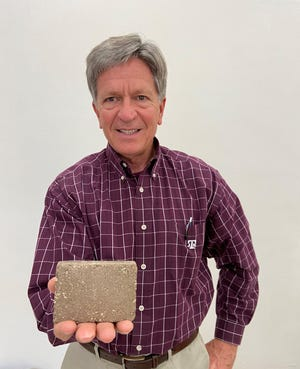 Lake Wichita Revitalization Committee chairman David Coleman holds a sample-size compressed earth block made from Lake Wichita material. Early testing shows the material is suitable for making CEBs. Actual CEBs are slightly larger than a regular brick.