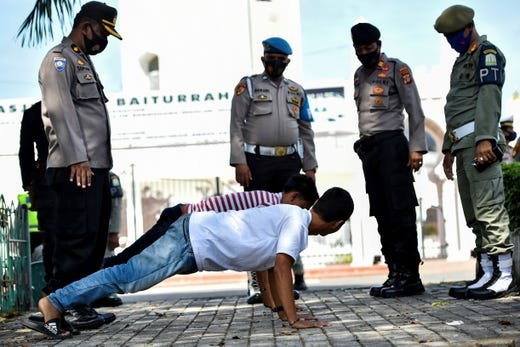 Members of the public perform push-ups as punishment for not wearing face masks amid the Covid-19 coronavirus pandemic in Banda Aceh on November 10, 2020.
