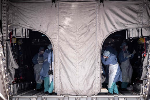 Members of the medical staff take care of Covid-19 patients aboard a French army Airbus A400 M before their transfer from Lyon-Bron aerodrome to the French capital Paris on November 10, 2020, amid a surge in Covid-19 (novel coronavirus) cases in France.