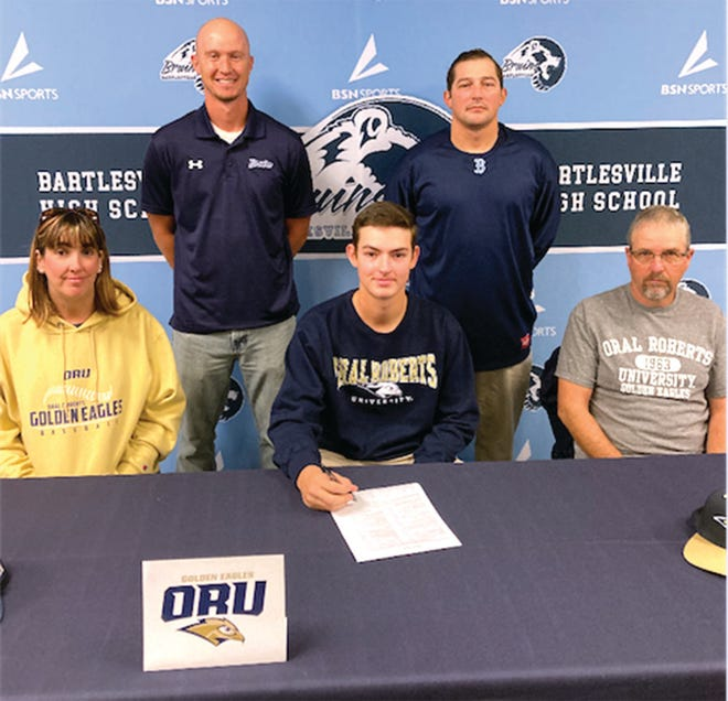 Jakob Hall, center, inks his letter of intent with Oral Roberts University. Seated are his parents April and Billy. Standing, from left, are Bartlesville High head coach Cody Price and assistant Ty Huie.
