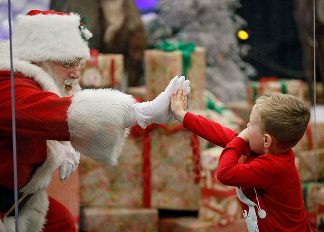 "Decker Dowdy, 3, touches Santa through a ""magic shield"" at the Polaris Cabela's on Nov. 10. The store requires timed appointments to see the jolly old elf."