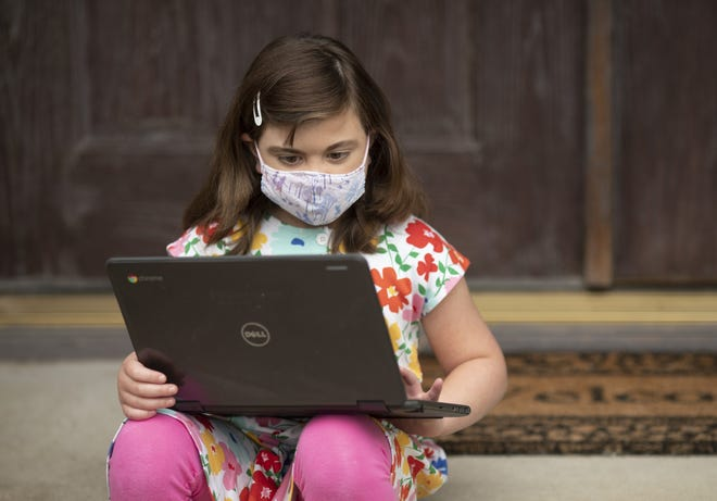 Lydia Parker, 9, sits at her Chromebook outside her Pickerington, Ohio home on Friday, Sept. 11, 2020. Parker, who is medically compromised, is enrolled in the Pickerington School District's online academy and takes all of her classes at home.
