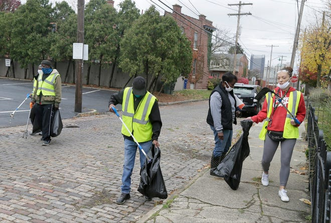 Volunteers, from left, Anthony Shanks, Larry Hergins, Ronald Tillman, Kim Hairston and Caroline Pyett, work to clean up Thurman Avenue in Columbus as part of the Cleaner Columbus effort recently funded by city council.