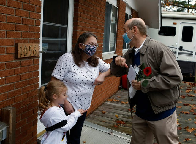 Michael Motil, an Army veteran and volunteer with Mount Carmel Hospice, bumps elbows to greet Pamela Caines as he delivers a rose for her and a handmade card for her husband, James, an Army veteran who did two tours in Vietnam and who is in hospice care at the couple's East Side home. Their granddaughter, 4-year-old Hayleigh Akers, looks on.