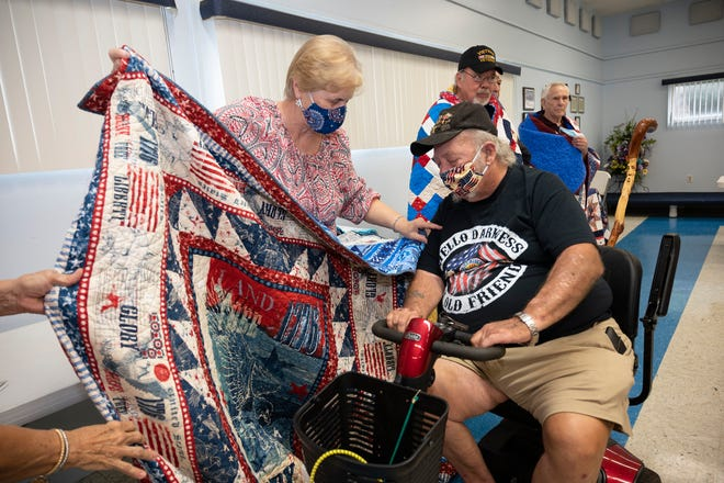 A veteran is presented a Quilt of Valor at the Quilting Sisters of Leesburg Veteran's Day presentation on Wednesday. [Cindy Peterson/Correspondent]